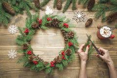 Woman making Christmas wreath using fresh natural materials. Workshop. Xmas. Workshop. royalty free stock image
