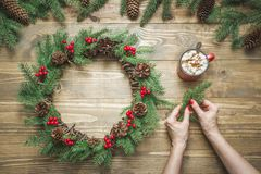 Woman making Christmas wreath using fresh natural materials. Workshop. Xmas. Workshop. stock photography