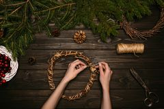 Woman making Christmas wreaths. Top view of woman hands making Christmas wreaths with branches and pine cones on wooden tabletop Royalty Free Stock Photography