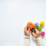 Woman making colored pompoms. View from above. White background. Royalty Free Stock Photography