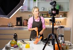 Woman making cooking vlog, recording herself on camera royalty free stock photo