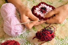 A woman is making a crochet pattern. stock images