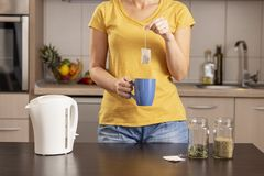 Woman making a cup of tea. In the morning, holding a cup and adding a teabag into a boiling water from a kettle royalty free stock photography