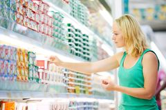 Woman making dairy shopping. Woman choosing produces in dairy shopping mall Stock Images