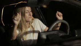 Woman making dance moves at night in car