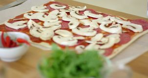 Woman making a delicious pepperoni pizza. Woman making a delicious homemade pepperoni pizza placing sliced mushrooms on the salami and tomato paste on her stock footage