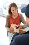 Woman making a digital signature for receiving a package Royalty Free Stock Photo