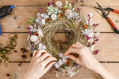 Woman making door wreath with autumn plants and flowers Royalty Free Stock Image