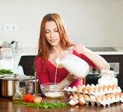 Woman  making dough or omlet in  kitchen Stock Photos