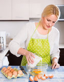 Woman making dough or omlet Royalty Free Stock Image