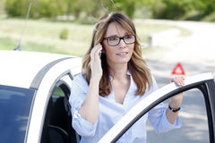 Woman making emergency call on the road. Close-up portrait of confident middle aged woman using her mobile phone while standing on the road at her broken down Stock Photos