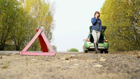 The woman making emergency call to recovery services with broken car. Warning triangle on country road stock footage