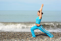 Woman is making exercise on sea Royalty Free Stock Photography