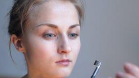 Woman making eyebrow correction stock footage