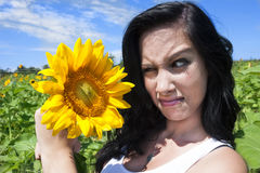Woman making face at sunflower Stock Photos