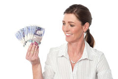 Woman making fan of pound sterling banknotes Stock Photography