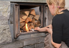 Woman making fire on fireplace Stock Photography