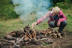Woman making fire in mountain camp royalty free stock photos