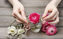 Woman making floral wedding decorations. Tiny bouquet of beautiful pink flowers Stock Photos