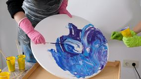Woman making fluid art acrylic painting. Creative cosmic artwork hippie wallpaper in blue color with hands of creator. Woman make fluid artwork. Fluid art stock video footage