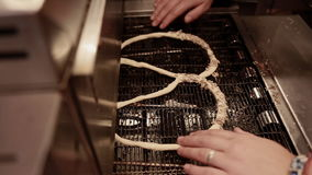 Woman making fresh pretzels with sunflower and sesame seeds in the bakery. Baking buns on the production line in the baking industry stock footage