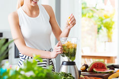 Woman making fruit cocktail Stock Image