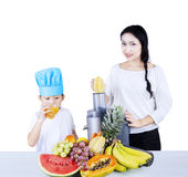 Woman making fruit juice to a boy Royalty Free Stock Photography