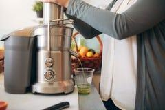 Woman making fruit juice using juicer Royalty Free Stock Photos