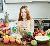 Woman making  fruit salad with cream. In home kitchen Royalty Free Stock Photography