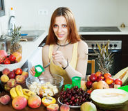 Woman making  fruit salad with cream. In  kitchen Stock Image
