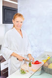 Woman making fruit salad in kitchen. Pretty woman making fruit salad in kitchen stock photo