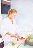 Woman making fruit salad in kitchen. Pretty woman making fruit salad in kitchen stock images
