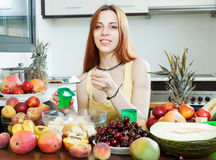 Woman making  fruit salad with yoghourt. Positive long-haired woman making  fruit salad with yoghourt in home kitchen Royalty Free Stock Images