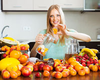 Woman making fruits beverages Royalty Free Stock Images