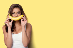 Woman making fun with a banana. Yellow background Royalty Free Stock Image