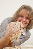 Woman making fun with dough. A smiling mature woman in her forties joking around with dough Stock Images