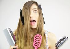 Woman making funny expression with combs and brushes in her long hair Royalty Free Stock Photography