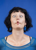 Woman making funny face. Middle-aged woman making funny faces - isolated on blue Royalty Free Stock Photography