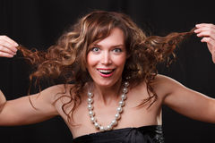 Woman making a funny face. Portrait of happy young woman doing a grimace and  taking her  hair Royalty Free Stock Photography