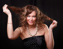 Woman making a funny face. Portrait of happy young woman smiling and taking her hair stock image