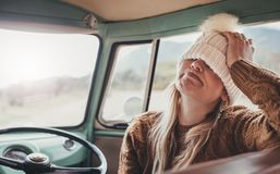 Woman making funny face on a road trip. Woman on a road trip. Young female wearing warm clothing sitting in van making funny face Royalty Free Stock Images