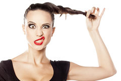 Woman making funny face. Young woman holding her hair and making funny face Royalty Free Stock Photo
