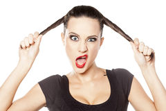 Woman making funny face. Young woman holding her hair and making funny face Royalty Free Stock Images