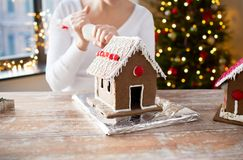Woman making gingerbread houses on christmas stock photos
