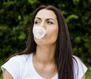 Woman making gum bubbles Royalty Free Stock Photos
