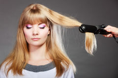 Woman making hairstyle with hair iron Stock Photo