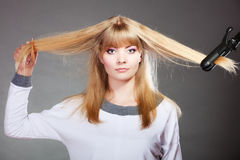 Woman making hairstyle with hair iron Royalty Free Stock Photography