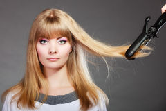 Woman making hairstyle with hair iron Royalty Free Stock Image