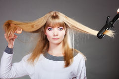 Woman making hairstyle with hair iron Stock Photography