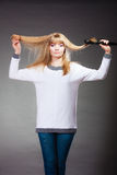 Woman making hairstyle with hair iron Stock Image